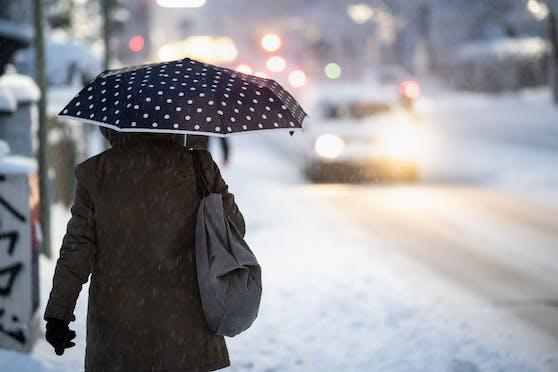 Eine Frau auf schneebedeckter Straße in Bayern. (Symbolbild)