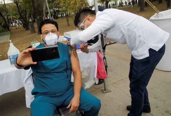 Ein Pfleger macht ein Selfie, nachdem er eine Impf-Dosis in einem Militärspital erhalten hat.