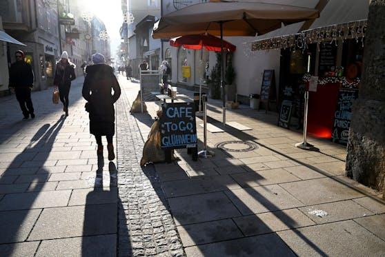 Passanten gehen im Gegenlicht in einer Einkaufsstraße. (Symbolbild)