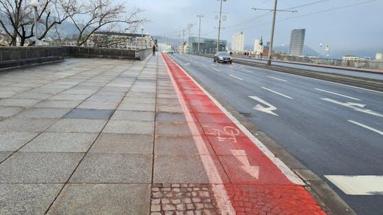 Weil der Granit der Fahrbahn die Farbe nicht gut aufnimmt, löst sie sich im Winter durch das Streusalz ab.