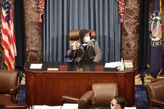 Auf einem anderen Bild posierte ein Demonstrant im geräumten Senatssaal mit erhobener Faust auf dem Platz des Kammervorsitzenden.