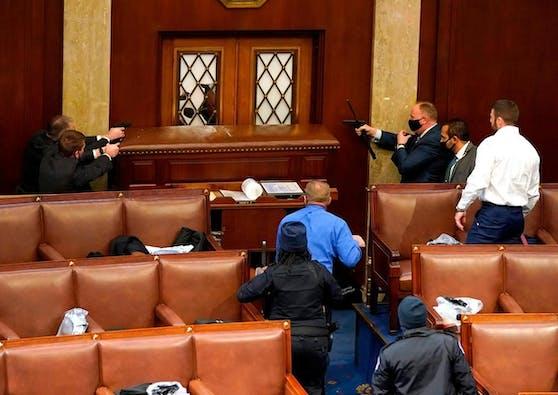Polizisten mit Waffen versuchen, die Randalierer am Eindringen in den Parlamentssaal zu hindern.