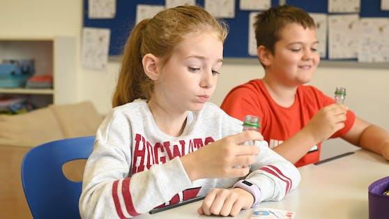Eine Schülerin und ein Schüler beim Gurgeltest