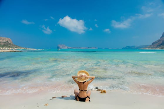 Young redhead girl in black bikini and with hat on Balos beach, west Crete, Greece. Summertime season vacation, July