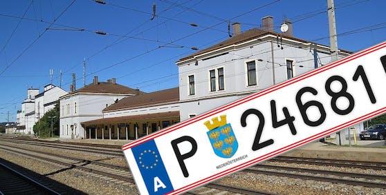 Symbolfoto eines Autokennzeichens und der Bahnhof Neulengbach im Hintergrund.