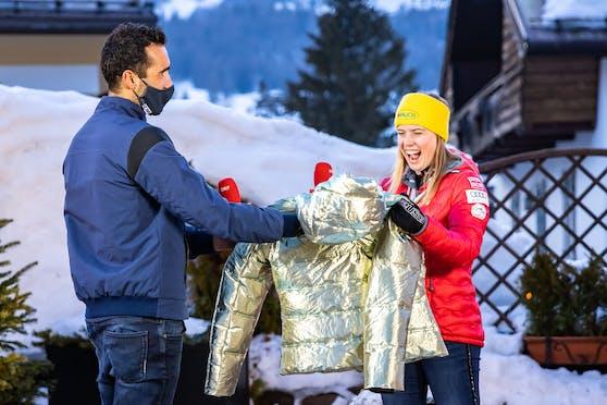 Martin Fourcade schenkt Katharina Liensberger eine goldene Jacke.