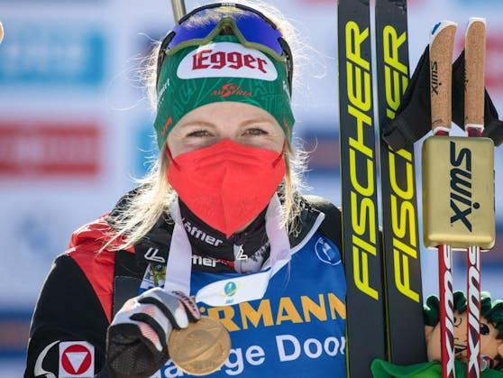 Lisa Hauser strahlt unter ihrer Maske mit der Goldenen um die Wette.