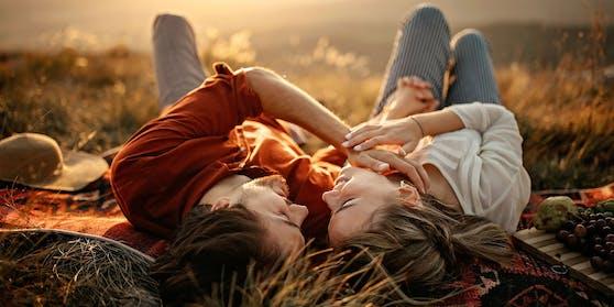 Ein Paar liegt auf einer Wiese. Symbolbild