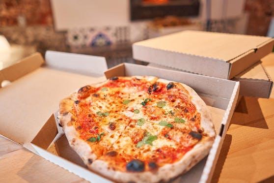 Eine Pizza wird zur Lieferung verpackt. Symbolbild