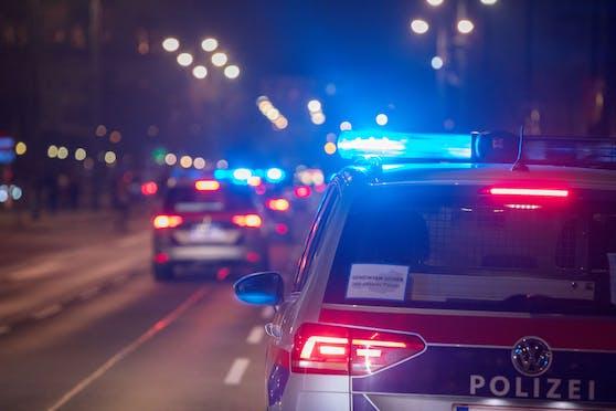 Polizeifahrzeuge mit Blaulicht bei einem nächtlichen Einsatz in Wien. Symbolbild