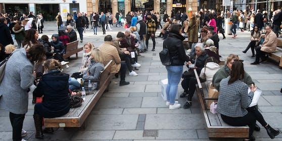 """Menschen stehen bei sonnigem Wetter mit Getränken an der Kreuzung Am Graben und der Einkaufstraße """"Kohlmarkt""""."""