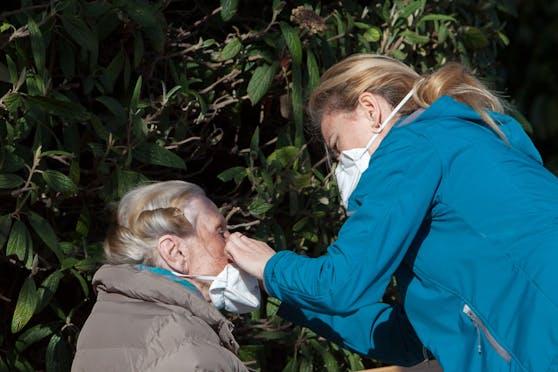 Eine Frau hilft einer älteren Frau bei aufsetzen der Schutzmaske im Stadtpark in Wien zu Ostern 2020. Auch 2021 wird angespannt.