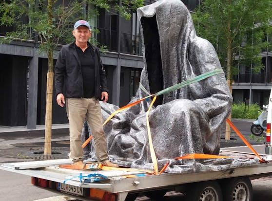 """Künstler Manfred Kielnhofer mit einer seiner """"Wächter der Zeit""""-Statue."""