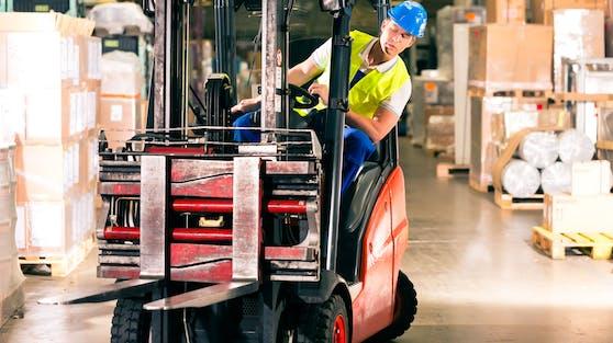Ein Arbeiter steuert einen Gabelstapler in einem Warenlager. Symbolbild