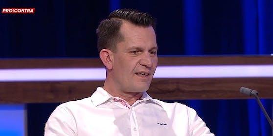 Wolfgang Mückstein im aufgeknöpften weißen Hemd