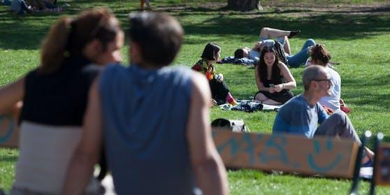 Menschen sitzen auf Bänken und am Rassen bei Sonnenschein im Stadtpark in Wien.