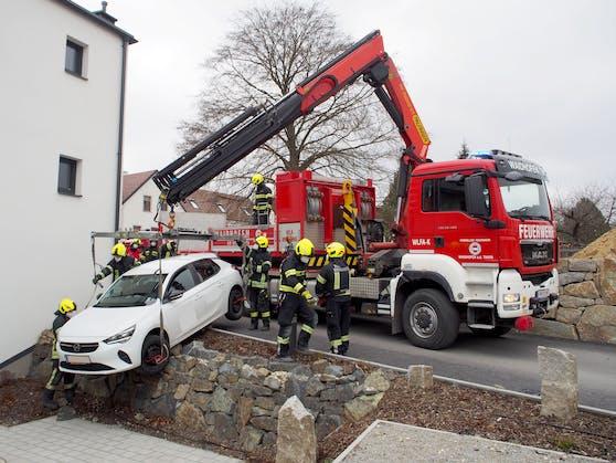 Die Feuerwehr hob den Wagen vorsichtig von der Mauer.