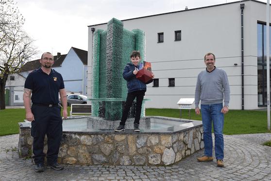 Der Neunjährige wurde von Feuerwehrkommandant Martin Denk und Bürgermeister Andreas Hammer gelobt.