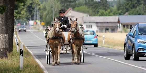 Symbolbild: Eine Zweispänner-Kutsche auf einer Landstraße in Deutschland.