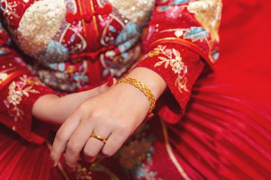 Traditionelles Hochzeitskleid und Schmuck in China. (Symbolbild)