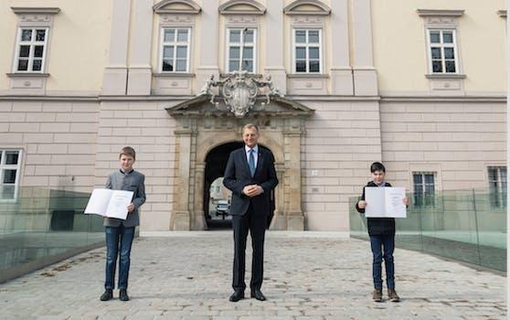 Hannes und Valentin mit den Urkunden vor dem Linzer Landhaus. LH Thomas Stelzer ehrte sie Donnerstagnachmittag für ihren Mut.