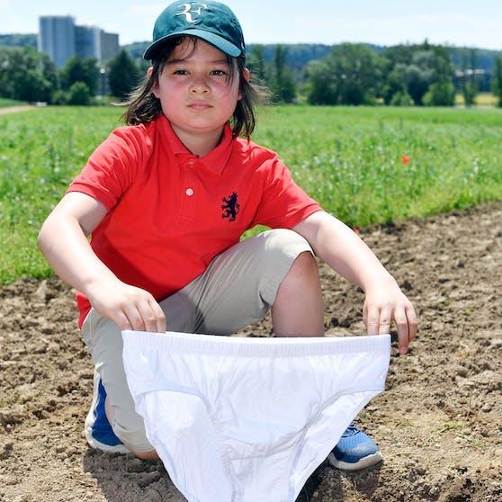 Der junge Arin vergräbt eine Unterhose auf dem Gelände von Agroscope.