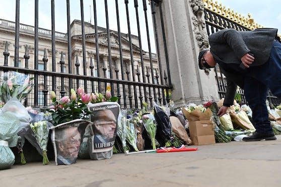 Passanten legen Blumen vor dem Buckingham Palace ab.