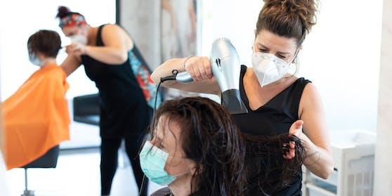 Eine Friseurin föhnt einer Kundin die Haare.