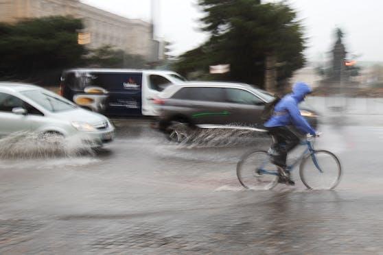 Radfahrer und Autos fahren über eine von starken Regen überflutete Straße am Museumsplatz in Wien. Archivbild