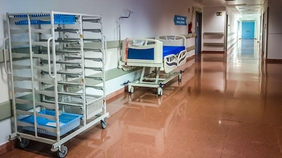 Ein Spitalsbett ist auf dem Gang einer Klinik abgestellt. Symbolbild