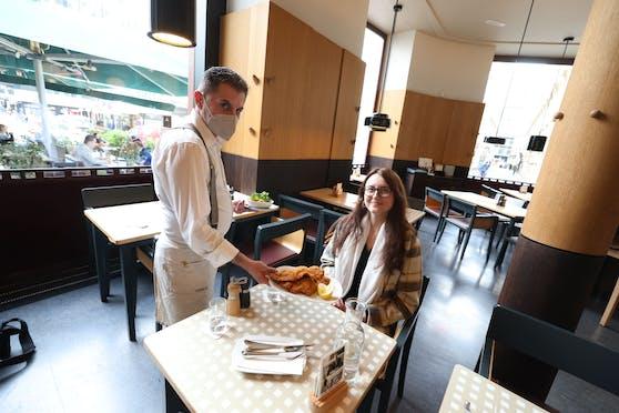 Kellner mit Maske serviert ein Wiener Schnitzel.
