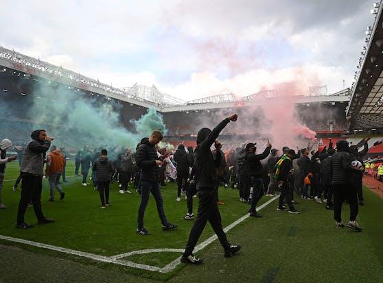 Tausende Manchester-United-Fans protestieren rund um das Old Trafford. Einige verschaffen sich sogar Zugang und stürmen den Rasen.
