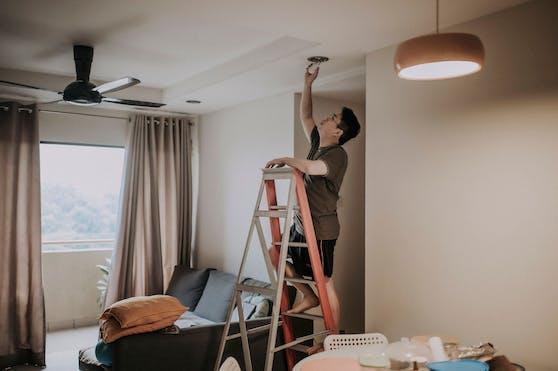 Ein Mann steht auf einer Leiter, um eine Glühbirne zu wechseln. Symbolbild