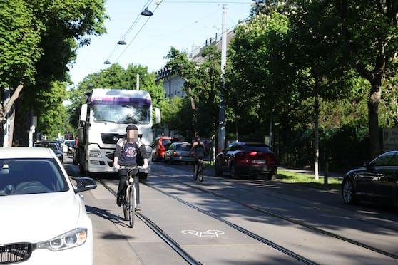 Rad-Piktogramme sollen Radfahrer dazu ermutigen, zwischen den Gleisen zu fahren. Entlang der Autos drohen Dooring-Unfälle.