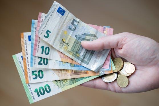 Eine Frau hält Bargeld in der Hand. (Symbolbild)
