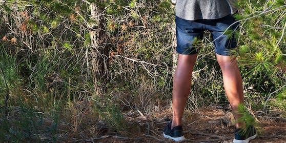 Ein Mann hat gegen einem Baum uriniert.