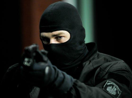 Ein Cobra-Beamter, maskiert und mit der Waffe im Anschlag.
