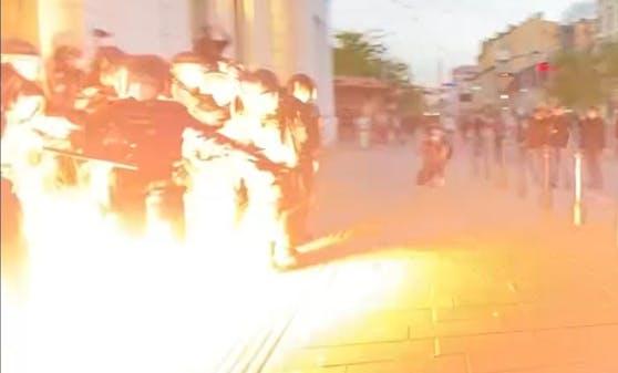 Die Szene zeigt einen explodierenden pyrotechnischen Gegenstand, der auf die Polizei geworfen wurde.