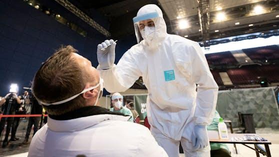 Ein Helfer mit speziellem Schutzanzug nimmt einen Corona-Testabstrich. Archivbild