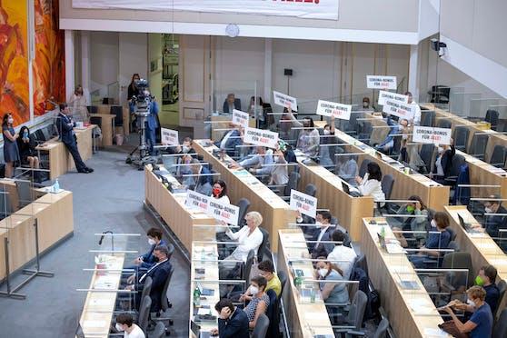 """Nationalratssitzung am 16. Juni: Abgeordnete halten Schilder mit der Aufschrift """"CORONA-BONUS FÜR ALLE!"""" in die Höhe."""