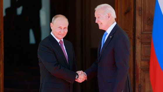 Russlands Präsident Wladimir Putin und US-Präsident Joe Biden reichen einander die Hände.