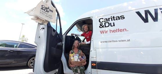 """Tamara und Niko stehen mit dem """"Wir helfen""""-Bus bei der SCS in Vösendorf."""