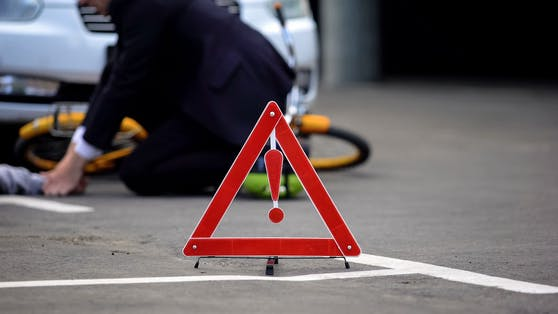Emergency red sign on road, male driver checking car crash victim pulse, death
