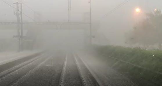 Lokführer filmt, wie Regen und Hagel gegen seinen Zug peitschen.