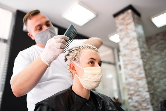 Eine junge Frau mit Schutzmaske beim Friseur. Ab 1. Juli ist diese in Österreich nicht mehr notwendig.