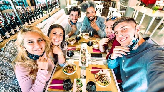 Freunde machen ein Selfie in einem Sushi-Restaurant: ab 10. Juni dürfen drinnen bis zu acht Erwachsene auf einem Tisch sitzen.