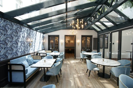 Passend zum Hellenic Fine Dining ist das Ambiente gediegen: Samtstühle, Marmortisch und Kunsttapete.