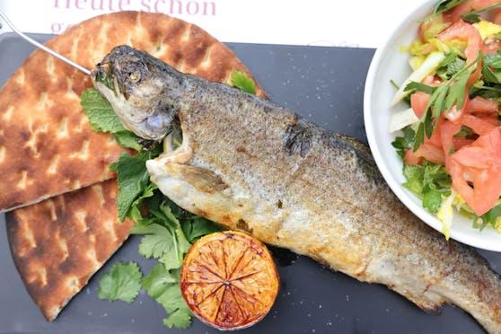 Zum Steckerlfisch (Forelle) serviert man Sommersalat, Pita und Grillzitrone.