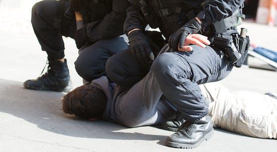Während der Festnahme musste der 21-Jährige von Polizisten auf dem Boden fixiert werden. (Symbolbild)