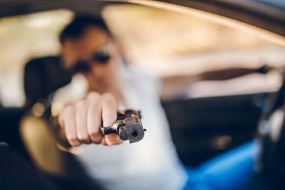 Ein junger Autofahrer richtet eine Waffe auf einen anderen Verkehrsteilnehmer. Symbolbild